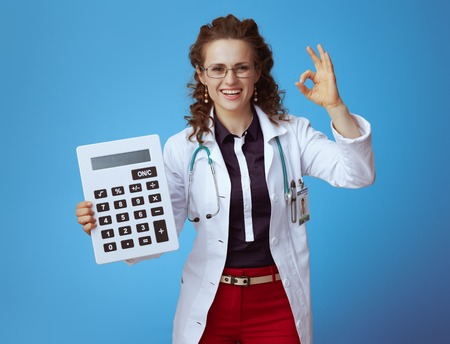 happy elegant doctor woman in bue shirt, red pants and white medical robe with big white calculator showing ok gesture isolated on blue.
