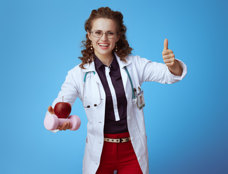 happy modern physician woman in bue shirt, red pants and white medical robe with dumbbell and apple showing thumbs up against blue background. Stock Photo