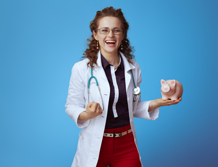 happy modern medical practitioner woman in bue shirt, red pants and white medical robe with piggy bank rejoicing against blue background.