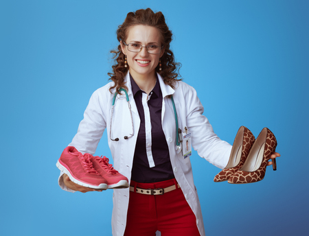 smiling elegant medical doctor woman in bue shirt, red pants and white medical robe showing fitness sneakers and high heel shoes isolated on blue.