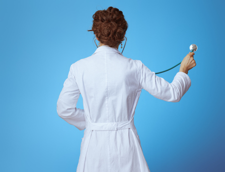 Seen from behind modern medical doctor woman in bue shirt, red pants and white medical robe listening with stethoscope against blue background.