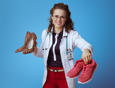 happy elegant physician woman in bue shirt, red pants and white medical robe giving fitness sneakers while holding high heel shoes in other hand isolated on blue background. Stock Photo