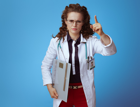 happy elegant doctor woman in bue shirt, red pants and white medical robe with weight scale threatening with finger on blue background.