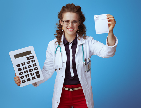 happy modern medical doctor woman in bue shirt, red pants and white medical robe with big white calculator showing prescription against blue background.