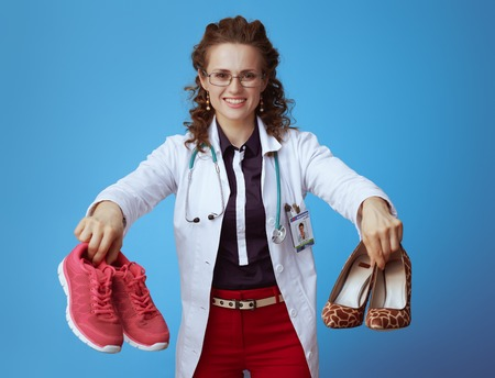 smiling modern medical practitioner woman in bue shirt, red pants and white medical robe showing fitness sneakers and high heel shoes against blue background.