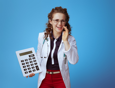 happy elegant medical practitioner woman in bue shirt, red pants and white medical robe with big white calculator telling exciting news isolated on blue. Stock fotó