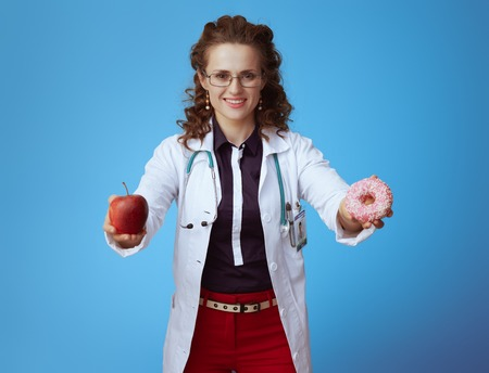smiling elegant physician woman in bue shirt, red pants and white medical robe showing apple and donut isolated on blue background.
