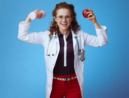 smiling elegant medical practitioner woman in bue shirt, red pants and white medical robe with dumbbell and apple showing biceps isolated on blue.