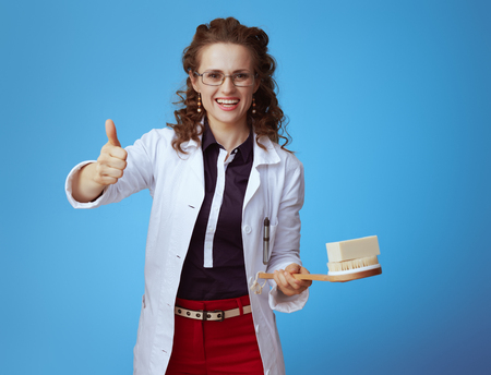 happy elegant physician woman in bue shirt, red pants and white medical robe with soap bar and bath brush showing thumbs up on blue background.