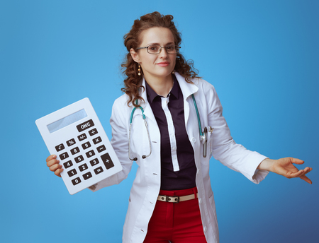 doubting modern medical doctor woman in bue shirt, red pants and white medical robe with big white calculator shrug isolated on blue.