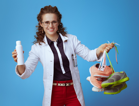happy modern medical practitioner woman in bue shirt, red pants and white medical robe showing fitness sneakers and shoe deodorizer spray against blue background.