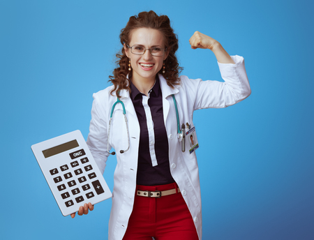 happy elegant medical doctor woman in bue shirt, red pants and white medical robe with big white calculator showing biceps against blue background.