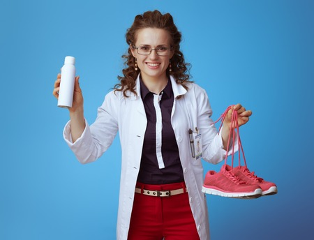 happy elegant doctor woman in bue shirt, red pants and white medical robe showing fitness sneakers and shoe deodorizer spray isolated on blue background. Stock Photo
