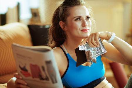 Portrait of dreamy fit woman in fitness clothes with chocolate bar and journal at modern home.
