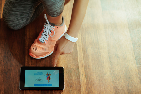 Closeup on healthy woman in sport clothes at modern home using online coaching fitness app in tablet PC.
