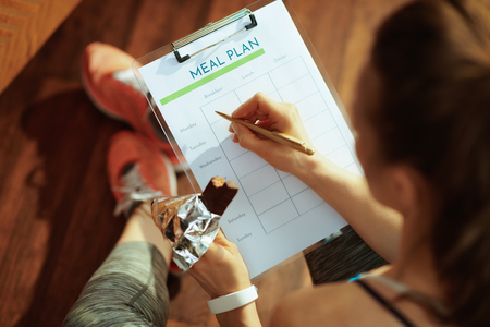 Seen from behind fit sports woman in sport clothes with chocolate raw protein bar filling meal plan in the modern living room. Stock Photo
