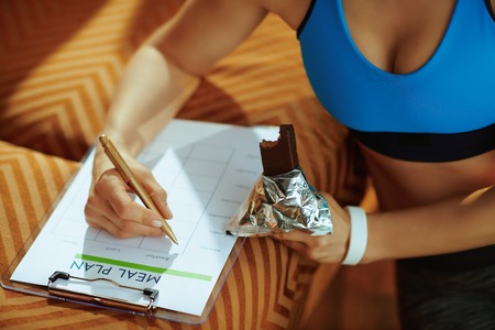 Closeup on young woman in fitness clothes with chocolate raw protein bar filling meal plan in the modern house.