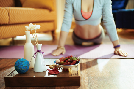 Closeup on tray with fragrant stuff for aroma yoga and fit woman doing yoga in background at modern home. Imagens