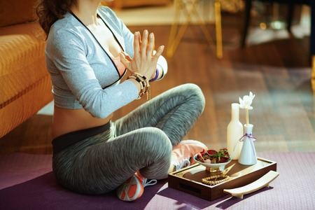 Closeup on active sports woman in sport clothes at modern home meditating.