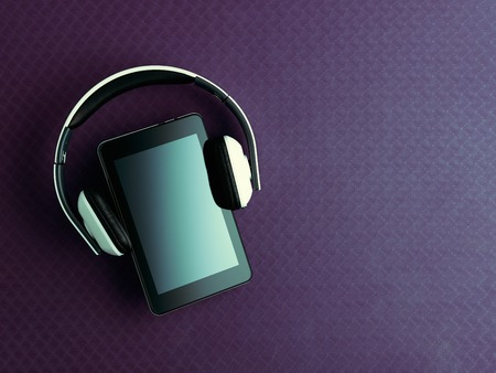 Closeup on white headphones and tablet PC laying on purple fitness mat. Flat Lay.