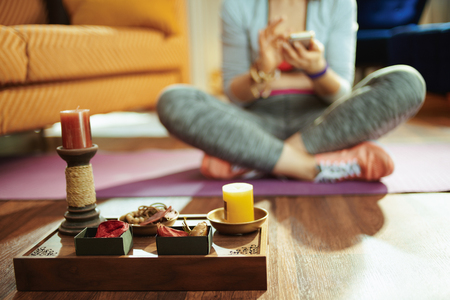 Closeup on tray with fragrant stuff for aroma yoga and fit woman watching yoga tutorial on internet via smartphone in the modern living room. Stock Photo