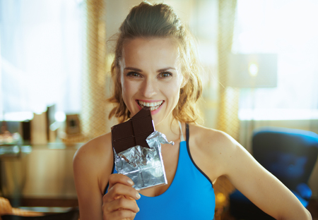 Portrait of happy young sports woman in fitness clothes in the modern house biting chocolate bar.