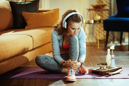 pensive active woman in sport clothes listening to the music with headphones in the modern house.