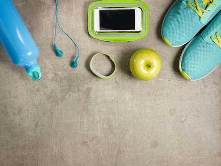 Closeup on laying on the floor green apple, headphones, sneakers, fitness tracker, bottle of water.
