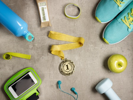 Closeup on laying on the floor green apple, dumbbell, headphones, elastic band, raw protein bar, sneakers, fitness tracker, bottle of water, smartphone in running armband and gold medal.