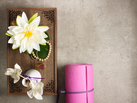 Closeup on tray with fragrant stuff for aroma yoga, beads and pink yoga mat laying on the floor. Stockfoto