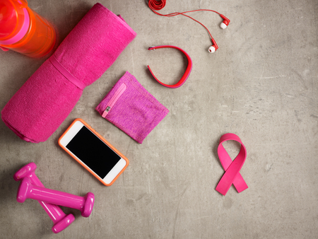 Closeup on laying on the floor pink dumbbells, towel, bottle of water, headphones, fitness tracker, armlet, smartphone and pink ribbon shaped elastic band.