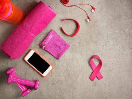 Nahaufnahme beim Auflegen auf dem Boden rosa Hanteln, Handtuch, Flasche Wasser, Kopfhörer, Fitness-Tracker, Armbinde, Smartphone und rosafarbenes Band geformtes Gummiband.