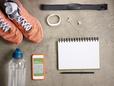 Closeup on sneakers, heart rate monitor, bottle of water, white fitness tracker, headphones, smartphone with gps activity tracking app and opened notebook with black pen laying on the floor.