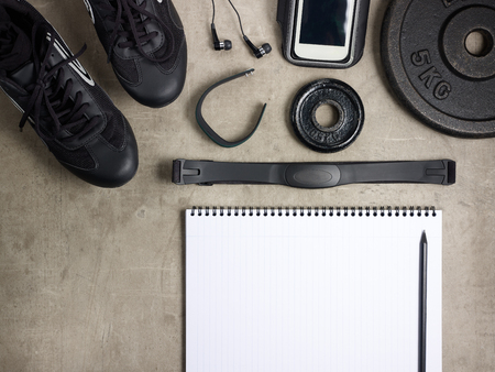 Closeup on laying on the floor black sneakers, headphones, fitness tracker, bottle of water, weight plate and opened notebook with pen Reklamní fotografie - 122620486
