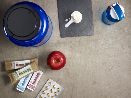Closeup on big blue protein jar, shaker, measuring spoon with powder, raw protein bars, red apple, sport supplements in tablets laying on the floor.