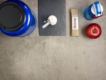 Closeup on big blue protein jar, shaker, measuring spoon with powder, raw protein bar, red apple laying on the floor.