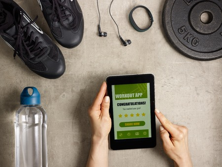 Closeup on black sneakers, headphones, fitness tracker, bottle of water, weight plate laying on the floor and female hands holding tablet PC with workout app offer to share result in social media.