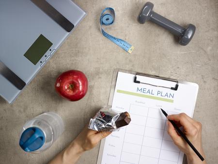 Close-up op gewichtsschalen, grijze halter, rode appel, fles water, meetlint op de vloer en vrouwelijke handen met gebeten rauwe eiwitreep die maaltijdplan vult.