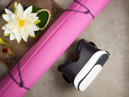 Closeup on tray with fragrant stuff for aroma yoga, beads, yoga mat and VR glasses laying on the floor. Imagens