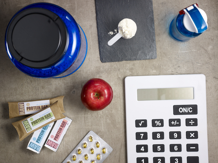 Closeup on big blue protein jar, shaker, measuring spoon with powder, raw protein bars, red apple, sport supplements in tablets and calculator laying on the floor.