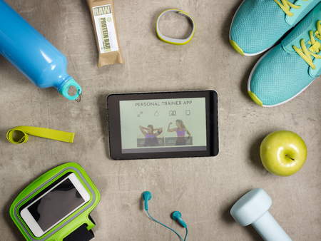 Closeup on green apple, dumbbell, headphones, elastic band, raw protein bar, sneakers, fitness tracker, bottle of water, smartphone in running armband and tablet PC with trainer app laying on floor. Stock Photo