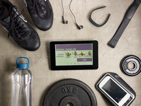 Closeup on black sneakers, headphones, fitness tracker, hear rate monitor, smartphone in running armband, bottle of water, weight plate and tablet PC with personal trainer app laying on the floor.