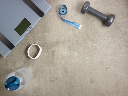 Closeup on laying on the floor weight scales, grey dumbbell, white fitness tracker, bottle of water, tape measure. Stock Photo