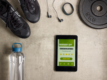 Closeup on black sneakers, headphones, fitness tracker, bottle of water, weight plate and tablet PC with workout app offer to share result in social media laying on the floor.