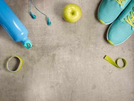 Closeup on laying on the floor green apple, headphones, elastic band, sneakers, fitness tracker, bottle of water. Stock Photo