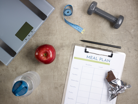 Closeup on weight scales, grey dumbbell, red apple, bottle of water, tape measure, bitten raw protein bar, black pen and clipboard with meal plan laying on the floor. Stock Photo