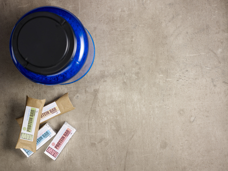 Closeup on laying on the floor big blue protein jar and raw protein bars.