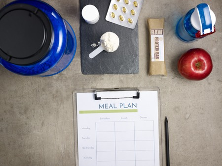 Closeup on big blue protein jar, shaker, measuring spoon with powder, raw protein bar, red apple, sport supplements in tablets, black pen and clipboard with meal plan laying on the floor.