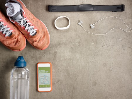 Closeup on sneakers, heart rate monitor, bottle of water, white fitness tracker, headphones, smartphone with gps activity tracking app laying on the floor.