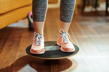 Closeup on fit sports woman in fitness clothes at modern home while training using balance board. Stock Photo